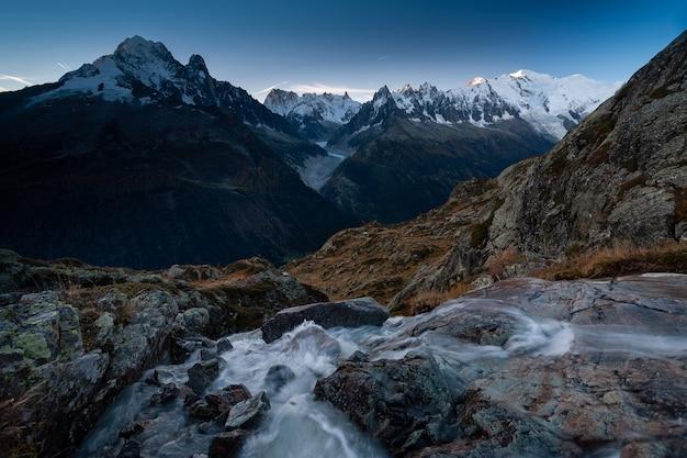 フランス、シャモニーの長時間露光の岩と川に囲まれたモンブラン山 無料写真