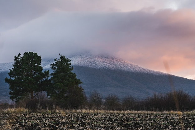 Mountain covered with snow and a cloudy sky during the sunset Free Photo