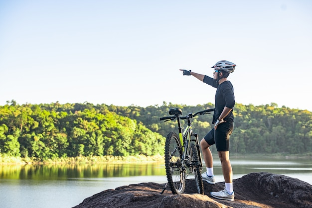 Mountain cyclists stand on the top of the mountain with the bike and point the finger in front. Free Photo