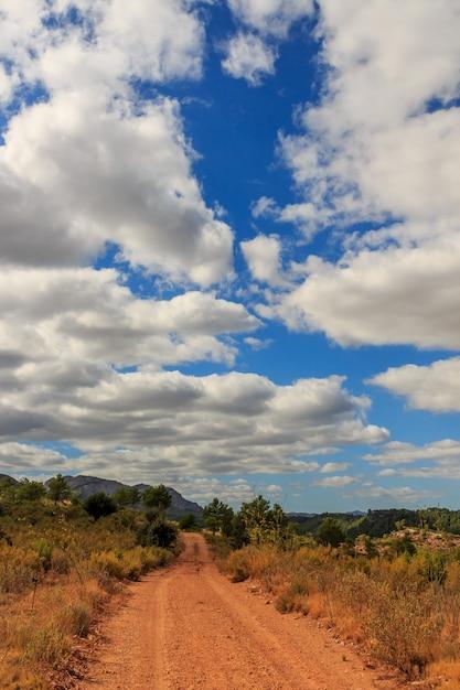 大きな雲と山の未舗装の道路自然要素の概念 Premium写真