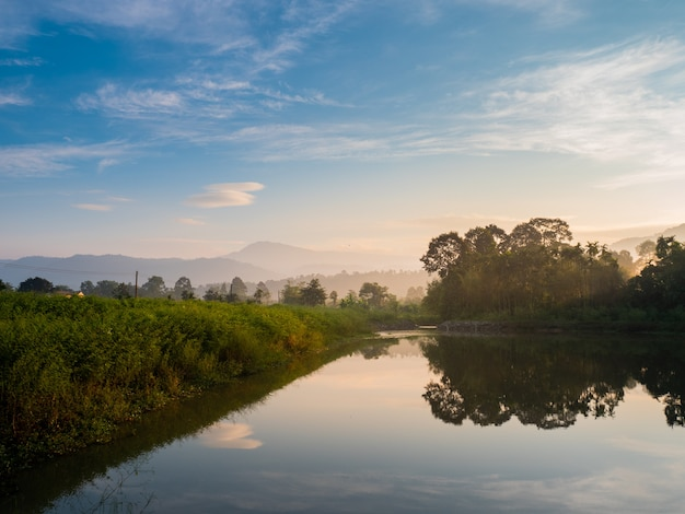 Mountain forest nature and reflectation on river with blue sky sunrise in the moning. Premium Photo
