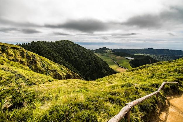 Горный пейзаж с пешеходной тропой и видом на красивые озера понта-делгада, остров сан-мигель, азорские острова, португалия. Бесплатные Фотографии