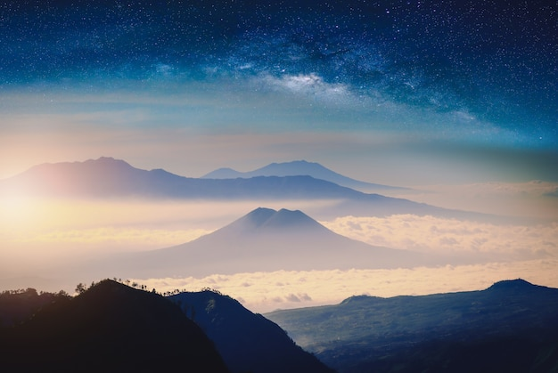 Mountain range in fog with sunlight and milky way galaxy. Premium Photo