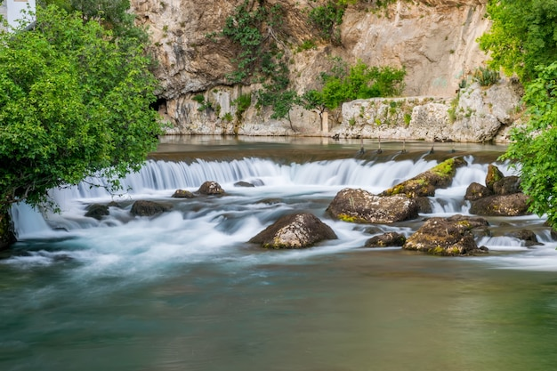 The mountain river formed a small waterfall among the stony rapids. Premium Photo