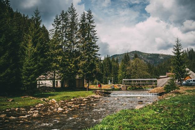Горная река в карпатском городе со старыми домами деревья мост Premium Фотографии