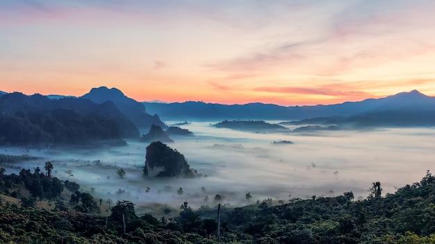 Восход горы с красивым драматическим небом. утренний туман в горной долине перед восходом солнца в зимний сезон. горный пейзаж фу лангка с утренним морем тумана на заднем плане Premium Фотографии