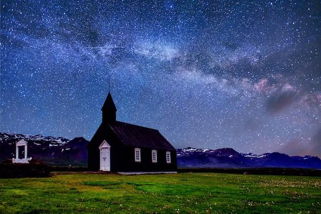마운틴 뷰 아이슬란드. 환상적인 별이 빛나는 하늘과 은하수. Budir에서 아름 다운 검은 목조 교회 무료 사진