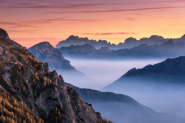 Mountains in fog at beautiful sunset in autumn Premium Photo