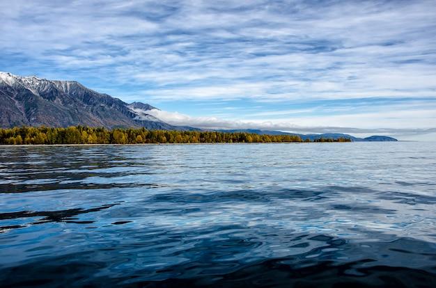 Горный пейзаж. облачное небо в пастельных тонах. романтический пейзаж. приморский вид с силуэтами синих холмов в тумане и осеннем лесу Premium Фотографии