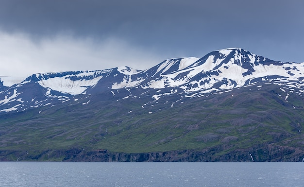 Mountains with snowy pics near the sea on a gloomy day in iceland Free Photo