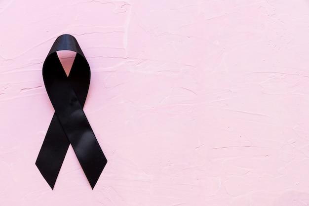 Mourning and melanoma black ribbon on pink background Free Photo