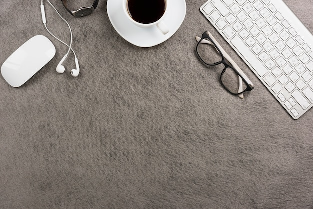 Mouse; keyboard; coffee cup; ear phone; wrist watch on gray background Free Photo
