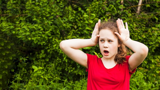 Mouth open girl child teasing with hand gesture at park looking away Free Photo