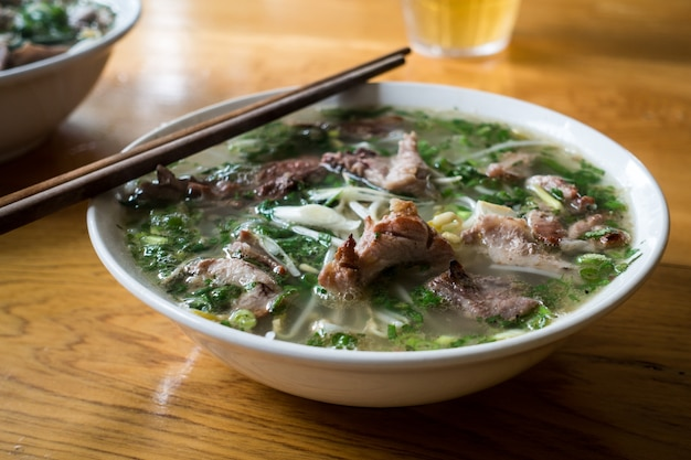 Mouthwatering vietnamese pho bo soup with chopsticks Free Photo