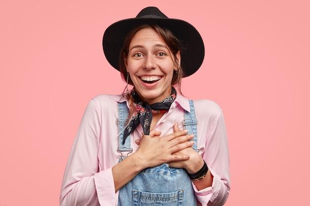 Подвижная красивая улыбчивая садовница держит обе руки на сердце, радуясь положительному комплименту, одетая в стильную одежду. Бесплатные Фотографии