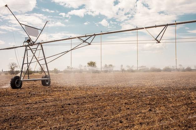 Перенесли оросительную систему на фермерское поле. Premium Фотографии