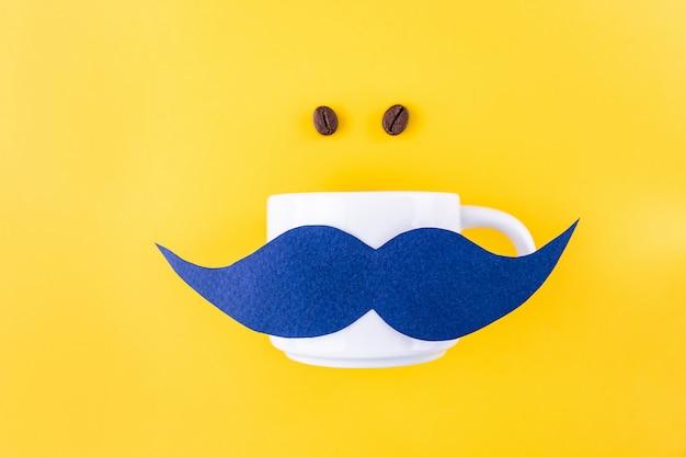 Movemberコンセプトのコーヒー穀物の横にあるコーヒーのマグカップに青い口ひげ Premium写真