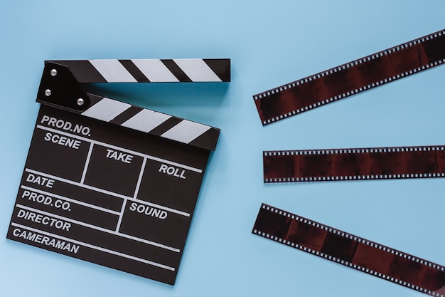 Movie clapper board with film on blue background for filming equipment Premium Photo
