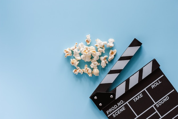 Movie clapper board with popcorn on blue background for entertainment Premium Photo