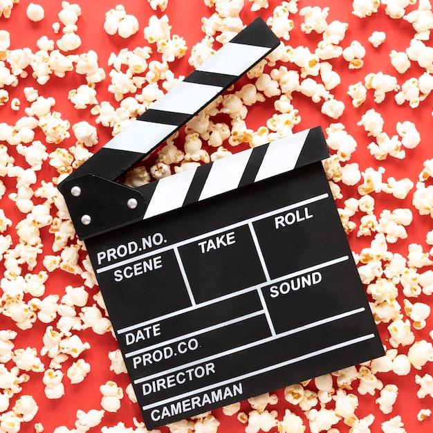 Movie clapper on red background with popcorn all around Free Photo