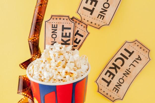 Movie tickets, film strips and popcorn on blue Premium Photo