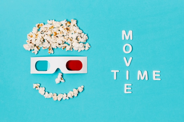 Movie time text with smiley anthropomorphic face made with popcorns and 3d glasses Free Photo