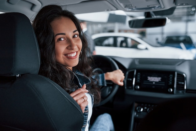 Moving backwards. ute girl with black hair trying her brand new expensive car in the automobile salon Free Photo