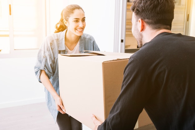 Moving concept with couple carrying box Free Photo