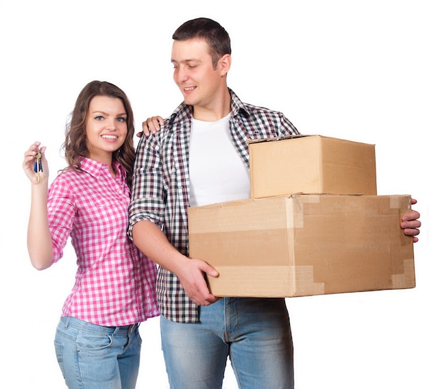 Moving, home and family concept - smiling couple holding cardboard boxes Premium Photo