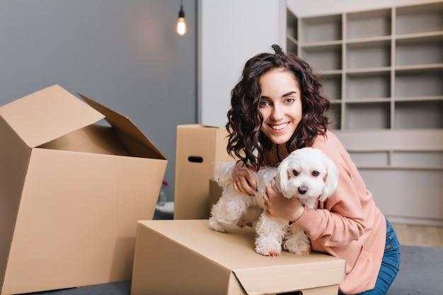 Trasferirsi nel nuovo appartamento di una giovane donna graziosa con un cagnolino. rilassarsi su scatole di cartone intorno al letto con animali domestici, sorridere, esprimere positività Foto Gratuite