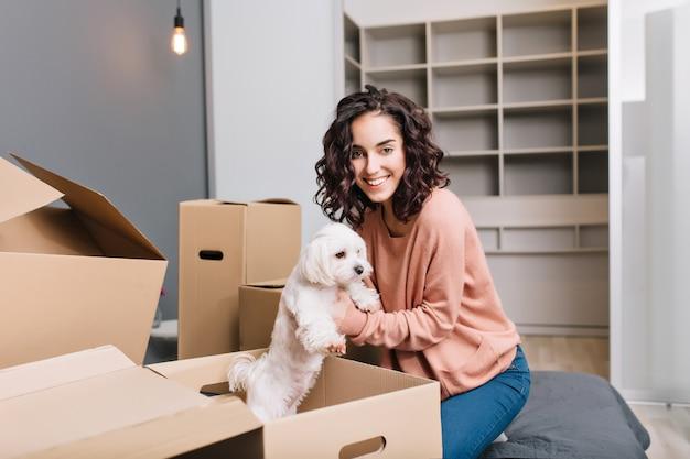 Переезд в новую современную квартиру веселая молодая женщина находит маленькую белую собачку в картонной коробке. улыбка красивой модели с короткими вьющимися волосами брюнетки в домашнем комфорте Бесплатные Фотографии
