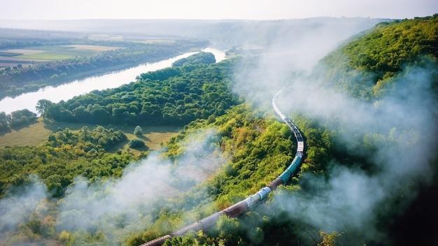 煙の高い柱、流れる川、丘、前景の鉄道のある鉄道で列車を動かす 無料写真