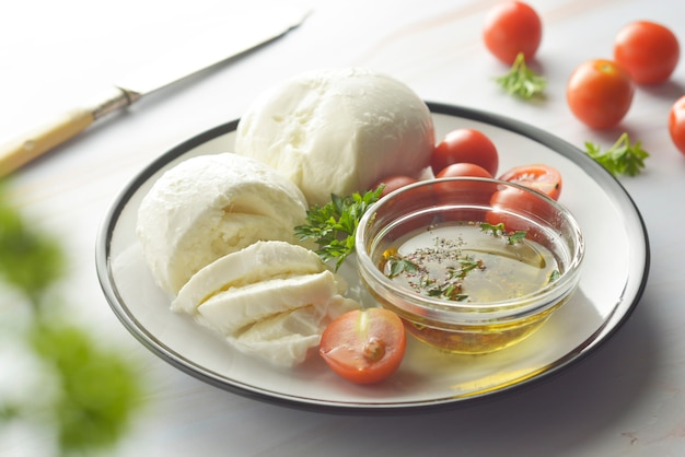 Mozzarella cheese and cherry tomatoes with spices. homemade mozzarella cheese. Premium Photo