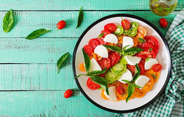 Mozzarella cheese, tomatoes and basil herb leaves in plate on the white wooden table Premium Photo
