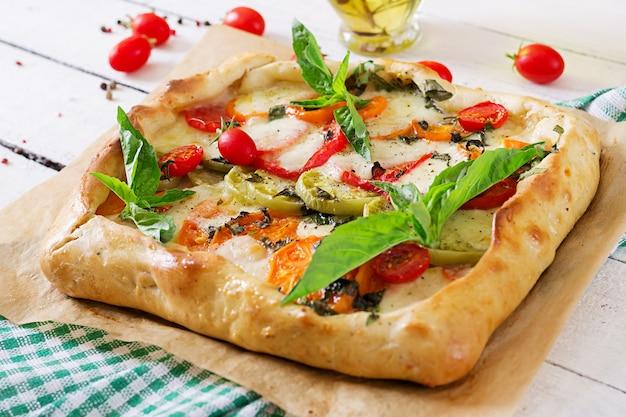 Mozzarella, tomatoes, basil savory pie on a white wooden table. delicious food, appetizer in a mediterranean style. Premium Photo