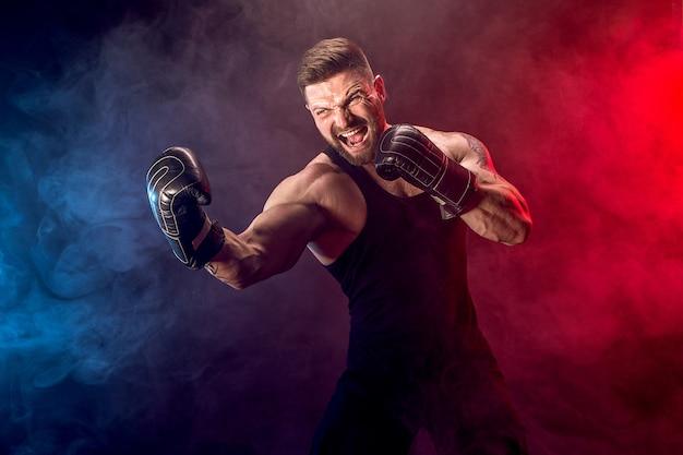 Боксер спортсмена muay тайский воюя на черной стене с дымом. Premium Фотографии