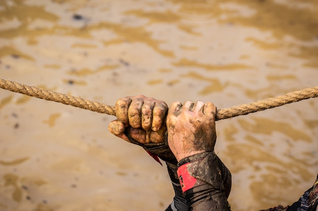 Mud race runners, defeating obstacles by using ropes. details of the hands. Premium Photo