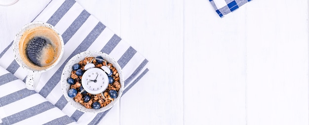 Muesli with blueberries in a cup and aromatic morning coffee. breakfast on a white wooden background and an alarm clock. flat lay. banner Premium Photo