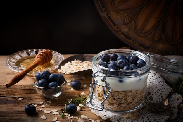 Muesli with yogurt and blue berries in glass jar. Premium Photo