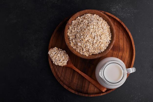 木製のカップにミューズリーを入れ、木製のプレートに牛乳の瓶を入れます。 無料写真