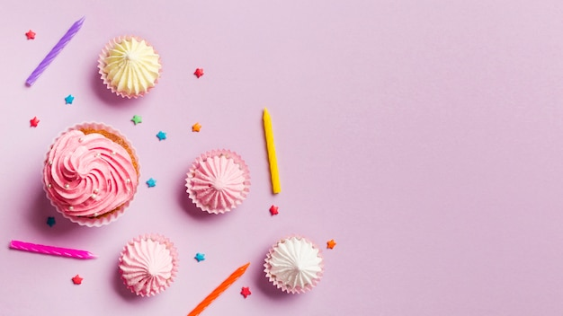 Muffins; candles; aalaw and sprinkles against pink background Free Photo