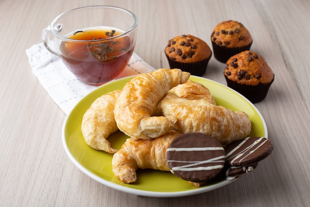 Muffins, cup of tea, croissants and caramel cookies Premium Photo
