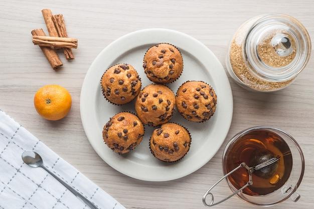 Muffins, cup of tea, sugar, tangerine and cinnamon Premium Photo