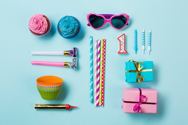 Muffins; sunglasses; party horn blowers; drinking straws; candle and gift boxes; sparkler on blue backdrop Free Photo