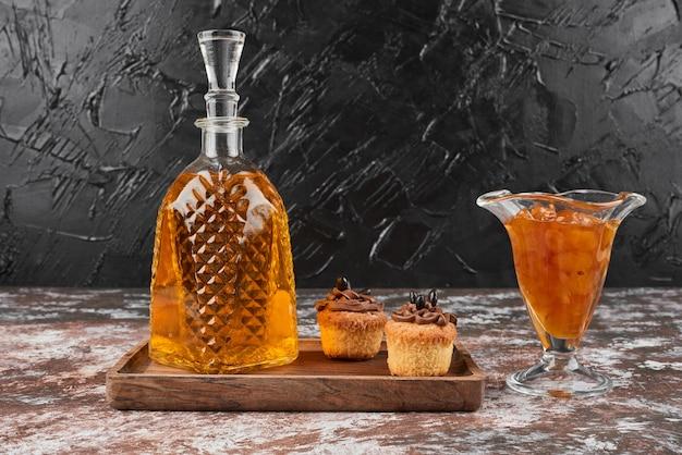 Маффины с конфитюром и напитком на деревянной доске. Бесплатные Фотографии
