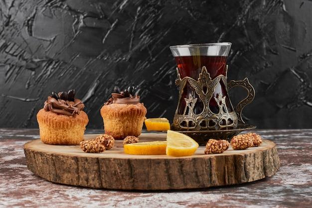 Muffin con bevanda su una tavola di legno. Foto Gratuite