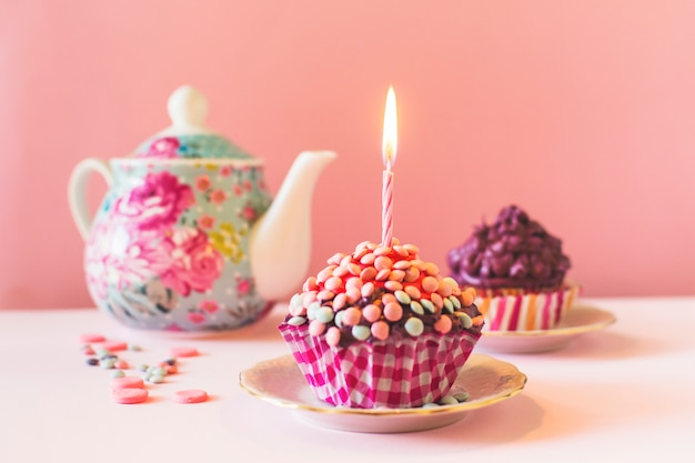 Muffins with illuminated candle on birthday Free Photo