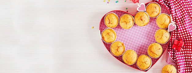 Muffins with pumpkin. cupcakes with valentine's day decor. flat lay. banner. top view. Premium Photo