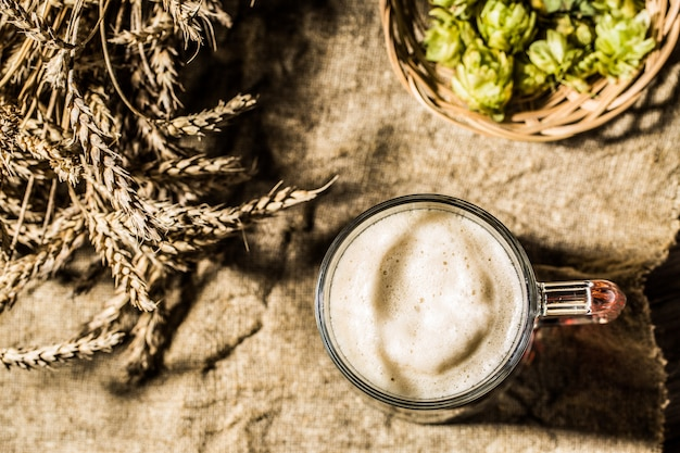 Mug beer with wheat and hops on linen cloth Premium Photo
