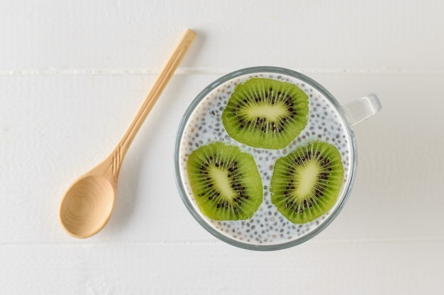 A mug of black chia seed pudding and three kiwi slices on a white wooden table. the view from the top. flat lay. Premium Photo